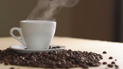 Close up of a white cup of evaporating coffee on table near roasted beans Stock Footage
