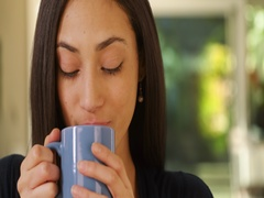 A Hispanic woman drinks her morning coffee Stock Footage