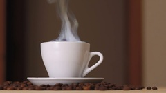 Close up of white cup of evaporating coffee on table near roasted beans. Slowly Stock Footage