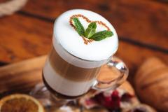 Latte with sweets on wooden table. Stock Photos