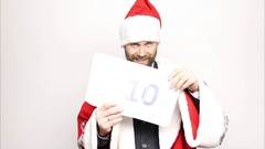 Businessman in a suit of Santa Claus holds a sheet of paper with numbers. final Stock Footage