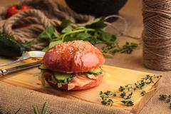 Trendy glossy burger with salmon in pink bun Stock Photos