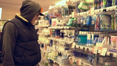 Young caucasian man shopping in a Supermarket and browsing products. Man Stock Footage