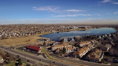 2016: aerial view of lake in suburban area, with dead grass and trees and blue Stock Footage