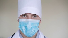 Close up of male surgeon's face dressed in surgical mask looking at camera in 4K Stock Footage