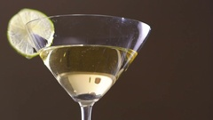 An olive falling into the goblet with the alcohol and slice of the lime. Slowly Stock Footage