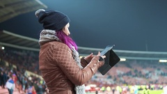 A fan girl taking pictures of a football game Stock Footage