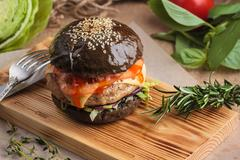 Trendy glossy burger with beef in black bun Stock Photos