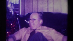 1973: man sitting in chair adjacent to christmas tree talking NEW YORK Stock Footage