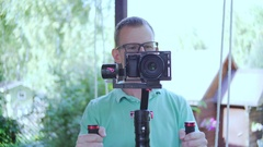 Camera Operator. The man will film with the video camera. Front view. The young Stock Footage