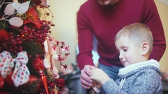 Man and his son decorate Christmas tree Stock Footage