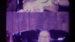 1973: split picture of a man sitting in a chair clutching a doll NEW YORK Stock Footage