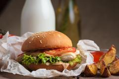 Classic burger with chicken and potato wedges Stock Photos