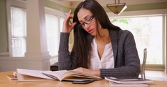 A college student does her homework in her living room Stock Footage