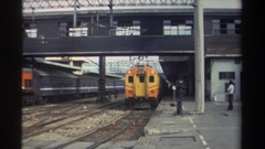 1982: passenger train leaving a station, passing under a catwalk HONG KONG Stock Footage