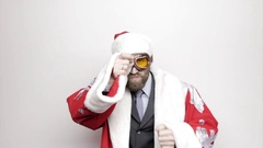 Businessman in a suit of Santa Claus wiping glasses raised hand to his eyes and Stock Footage