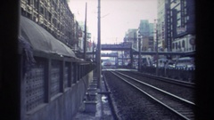 1982: electric train running on the track and vehicle are moving on road side Stock Footage