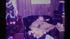 1973: a man opening his gift on christmas morning. NEW YORK Stock Footage