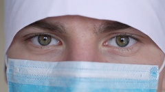 Close up of a male surgeon's face dressed in a surgical mask looking at camera Stock Footage