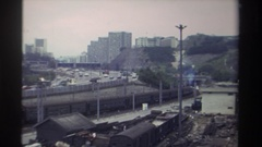 1982: vehicles and train curve on road and tracks between rail yard and city Stock Footage