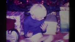 1973: toehead boy sitting on the floor with christmas presents NEW YORK Stock Footage