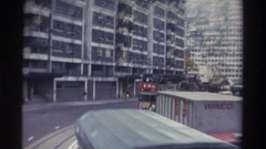 1982: an electric-powered, double-deck streetcar runs down a busy street in an Stock Footage