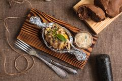 Baked potatoes with mushroom sauce served in foil Stock Photos