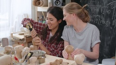 Woman Making Holes in Papier-Mache Toys Stock Footage