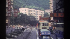 1982: double decker trolleys while walkers cross street HONG KONG Stock Footage