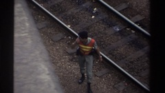 1982: a security guard walks in daylight along railroad tracks in a switchyard Stock Footage