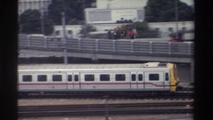 1982: silver train rolling along tracks at modest speed with cars driving in Stock Footage