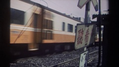 1982: train moving on a track with a sign adjacent written in asian language Stock Footage