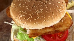 Fish Burger on a rotating wooden plate (seamless loopable; 4K) Stock Footage