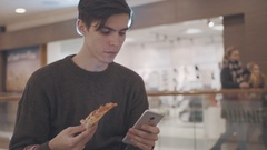 Young men using smartphone eat pizza and drink coke at shopping mall. Portrait Stock Footage