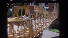 1965: wooden frame of an uncompleted boat near a brick house VOLMER YUCAIPA Stock Footage