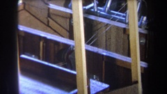 1965: pulley is centered between thin cords extending into large wooden Stock Footage