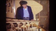 1965: older man check and then gluing to finish up his wooden structure. 1 Stock Footage