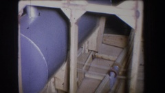 1965: a blueish-gray cylindrical tank is supported and enclosed in a wooden Stock Footage