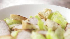Camera backwards fly over caesar salad with kumato tomatoes and follow falling Stock Footage