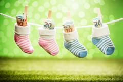 Pair Of Baby Sock With Dollar Hanging On Rope Stock Photos