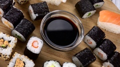 Sushi (with Soy Sauce) (rotating on a wooden plate; seamless loopable; 4K) Stock Footage