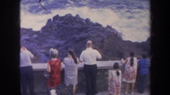 1967: people watching ocean waves behind a cement wall HAWAII Stock Footage