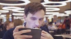 Young men using smartphone eat Shawarma roll at food court in shopping mall Stock Footage