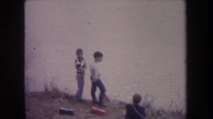 1968: a day at the lake with three boys wearing long sleeves and long pants Stock Footage