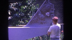 1969: man spray paints defaced public area for charity in the neighborhood Stock Footage