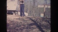 1968: man raking leaves in front of his silver trailer in the middle of the Stock Footage