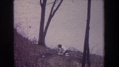1968: little girl at the lakeside in winter, playing with objects, old video Stock Footage