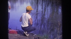 1968: two boys fishing in a pond, one catching a very small fish, taking it off Stock Footage