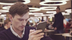 Young men using smartphone putting promo-code at food court in shopping mall Stock Footage