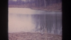 1968: two children on a cloudy day standing and squatting by a pond with Stock Footage
